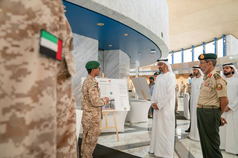 ABU DHABI, UNITED ARAB EMIRATES - April 28, 2019: HH Sheikh Mohamed bin Zayed Al Nahyan, Crown Prince of Abu Dhabi and Deputy Supreme Commander of the UAE Armed Forces (2nd R), attends e-skills exhibition for national service recruits, at Armed Forces Officers Club. Seen with HE Lt General Hamad Thani Al Romaithi, Chief of Staff UAE Armed Forces (R) and HE Mohamed Mubarak Al Mazrouei, Undersecretary of the Crown Prince Court of Abu Dhabi (back C). ( Mohamed Al Hammadi / Ministry of Presidential Affairs ) ---