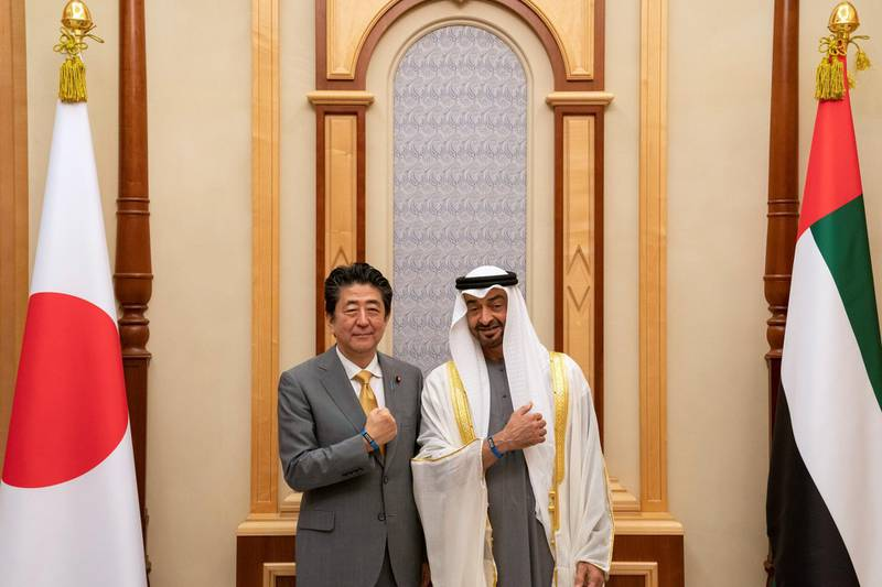 ABU DHABI, UNITED ARAB EMIRATES - January 13, 2020: HH Sheikh Mohamed bin Zayed Al Nahyan, Crown Prince of Abu Dhabi and Deputy Supreme Commander of the UAE Armed Forces (R) and HE Shinzo Abe, Prime Minister of Japan (L), stand for a photograph showing Expo 2020 bracelets, during a reception, at Qasr Al Watan.  ( Hamad Al Kaabi / Ministry of Presidential Affairs ) ---
