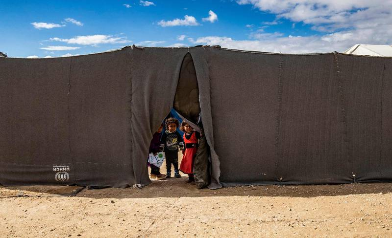 TOPSHOT - Children peek through the opening of a tent at the Kurdish-run al-Hol camp which holds suspected relatives of Islamic State (IS) group fighters, in the northeastern Syrian Hasakeh governorate, on February 17, 2021. / AFP / Delil SOULEIMAN