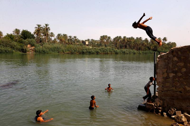Iraqi youths dive into the Euphrates river to take a swim and cool off, during increased temperatures in the holy city of Najaf, Iraq July 14, 2020. Picture taken July 14, 2020.  REUTERS/Alaa Al-Marjani