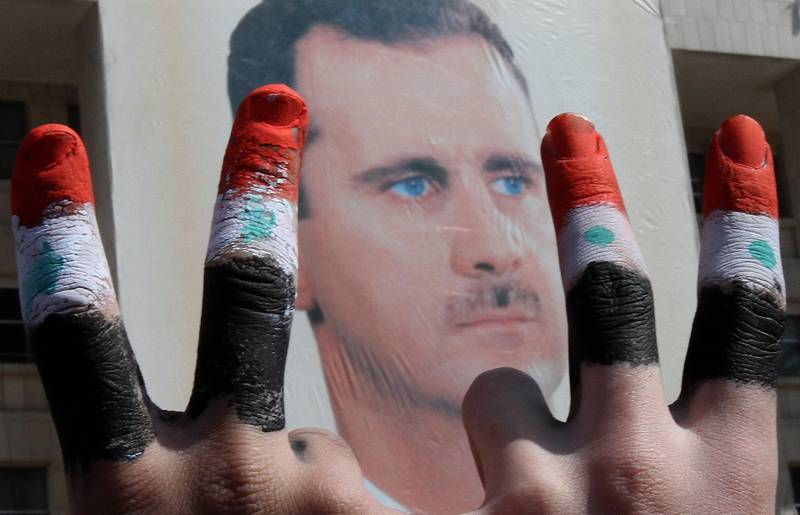 (FILES) In this file photo taken on March 29, 2011 Two men, with the fingers painted in the colours of the Syrian flag, show the V-sign as they pose in front of a huge image of President Bashar al-Assad during a rally by thousands supporters for their leader who is facing unprecedented domestic pressure amid a wave of dissent, in central Damascus.  -   / AFP / ANWAR AMRO