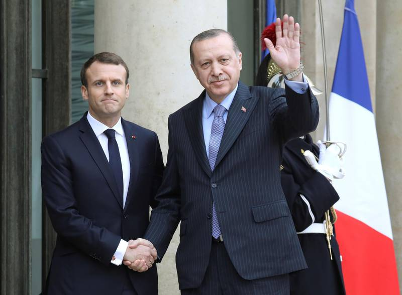"""(FILES) In this file photo taken on January 5, 2018 French President Emmanuel Macron (L) greets his Turkish counterpart Recep Tayyip Erdogan upon his arrival for their meeting and luncheon at the Elysee palace in Paris. Turkish President Recep Tayyip Erdogan slammed on October 24, 2020 his French counterpart, Emmanuel Macron, over his policies toward Muslims, saying that he needed """"mental checks."""" """"What can one say about a head of state who treats millions of members from different faith groups this way: first of all, have mental checks,"""" Erdogan said in a televised address.  / AFP / LUDOVIC MARIN"""