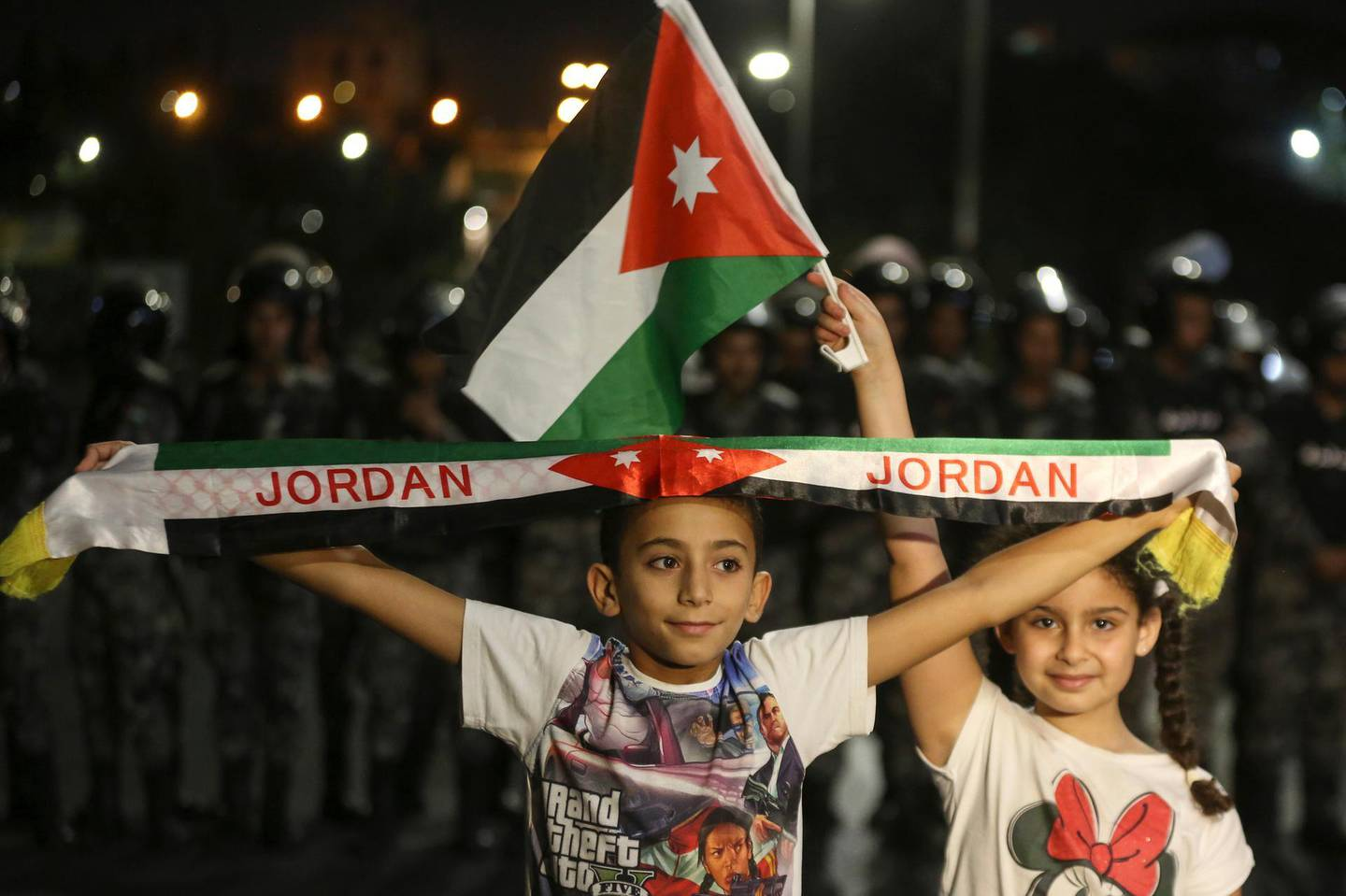 A girl and a boy hold a Jordanian flag and banner during a demonstration outside the Prime Minister's office in Amman, early Tuesday, June 6, 2018. Jordan's King Abdullah II on Tuesday appointed a new prime minister, the royal palace said, naming a leading reformer as head of government in hopes of quelling the largest anti-government protests in recent years.(AP Photo/Raad al-Adayleh)