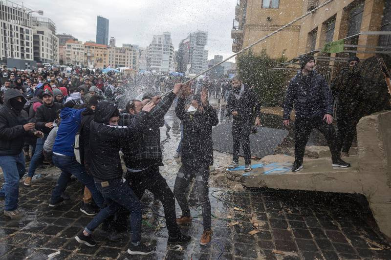 BEIRUT, LEBANON - FEBRUARY 11: Anti-government protesters are hit by a water cannon as they pull down a concrete barricade during a failed attempt to block politicians from accessing Parliament where they will vote whether to accept Lebanon's new government, on February 11, 2020 in Beirut, Lebanon. (Photo by Sam Tarling/Getty Images)