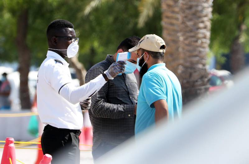 DUBAI, UNITED ARAB EMIRATES , May 5 – 2020 :- Security guard checking the temperature of the visitor at the Al Awir fruit & vegetable market in Dubai. UAE government ease the coronavirus restriction for the residents around the country. (Pawan Singh / The National) For News/Standalone/Online/Stock