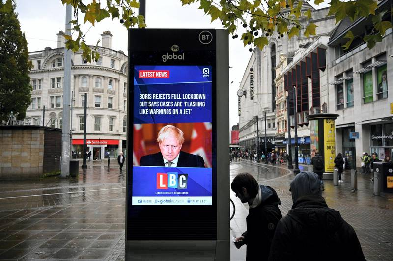 A news display features Britain's Prime Minister Boris Johnson as shoppers make their way along the streets of  Manchester, north west England on October 13, 2020, as the number of cases of the novel coronavirus COVID-19 continue to rise. - The British government faced renewed pressure on October 13, after indications it had ignored scientific advice three weeks ago for tougher restrictions to cut rising coronavirus infections. (Photo by Oli SCARFF / AFP)