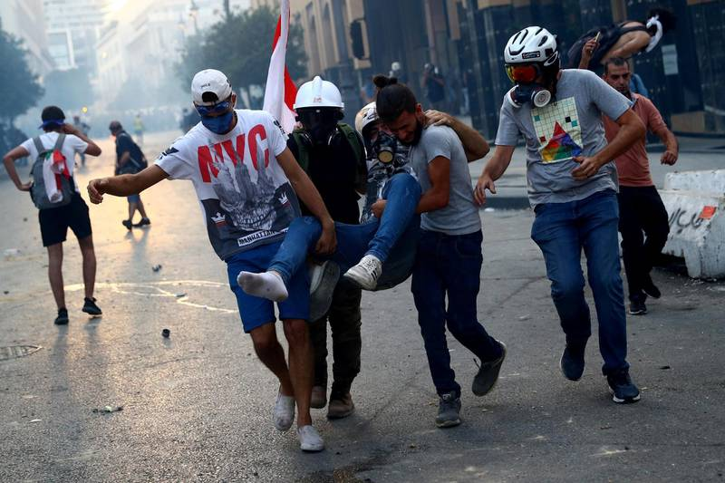 Demonstrators carry an injured man during anti-government protests that have been ignited by a massive explosion in Beirut, Lebanon, August 10, 2020. REUTERS/Hannah McKay     TPX IMAGES OF THE DAY