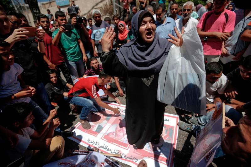 Employees of the UN Relief and Works Agency for Palestine Refugees in the Near East(UNRWA)and their families protest against job cuts announced by the agency outside its offices in Gaza City on July 31, 2018. / AFP PHOTO / SAID KHATIB