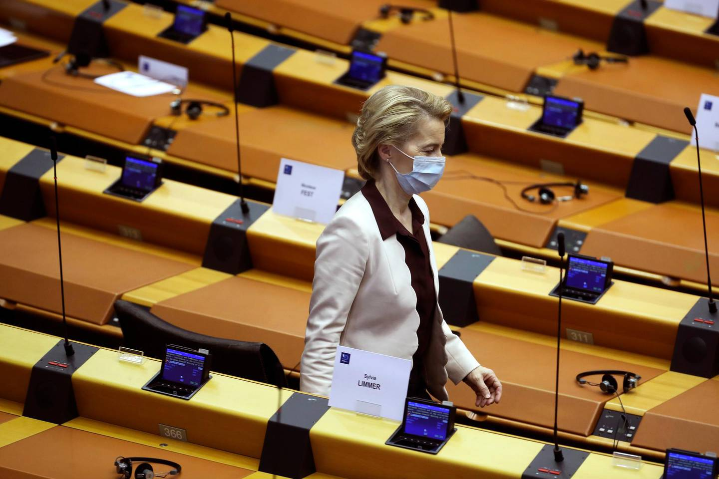 European Commission President Ursula von der Leyen wearing a mask to protect against coronavirus, leaves the main chamber of the European Parliament in Brussels, Thursday, July 23, 2020. European leaders took a historic step towards sharing financial burdens among the EU's 27 countries by agreeing to borrow and spend together to pull the economy out of the deep recession caused by the coronavirus outbreak. (AP Photo/Francisco Seco)