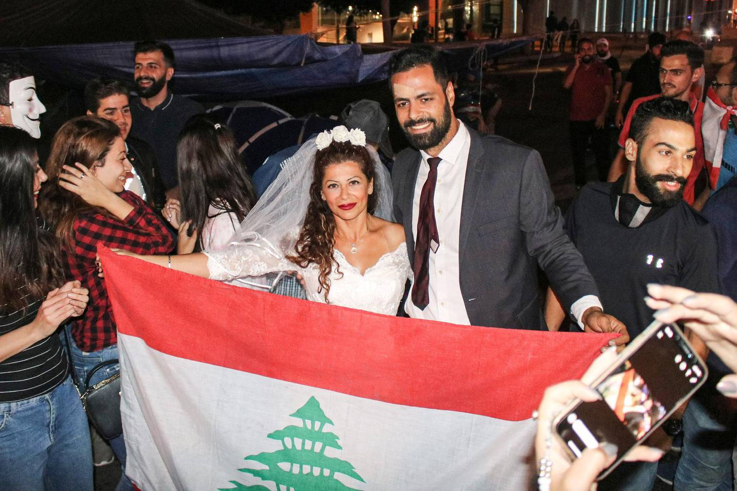 Malak Alaywe Herz, a woman who famously kicked the bodyguard of Education Minister Akram Chehayeb and became an icon in the current anti-government protests, poses for a picture in her wedding dress with a national flag alongside her newly-wed husband Mohammad after their marriage at Riad al-Solh square in the centre of the capital Beirut on October 23, 2019.  / AFP / Mohammad YASIN