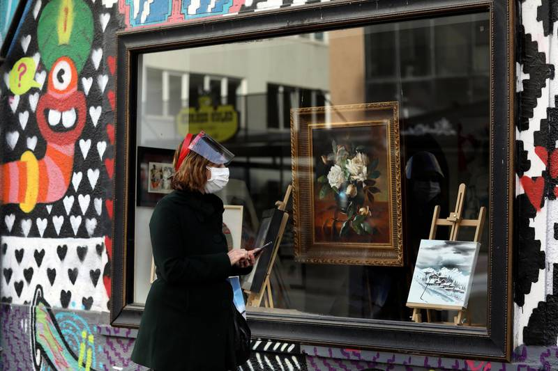 Semure Aras, wearing a mask to help protect against the spread of coronavirus, watches paintings displayed at the window of an art gallery, in Ankara, Turkey, Tuesday, Feb. 2, 2021. Turkey said last week it has detected the more infectious COVID-19 variant that was first found in southeast England, in 17 cities across the country. (AP Photo/Burhan Ozbilici)
