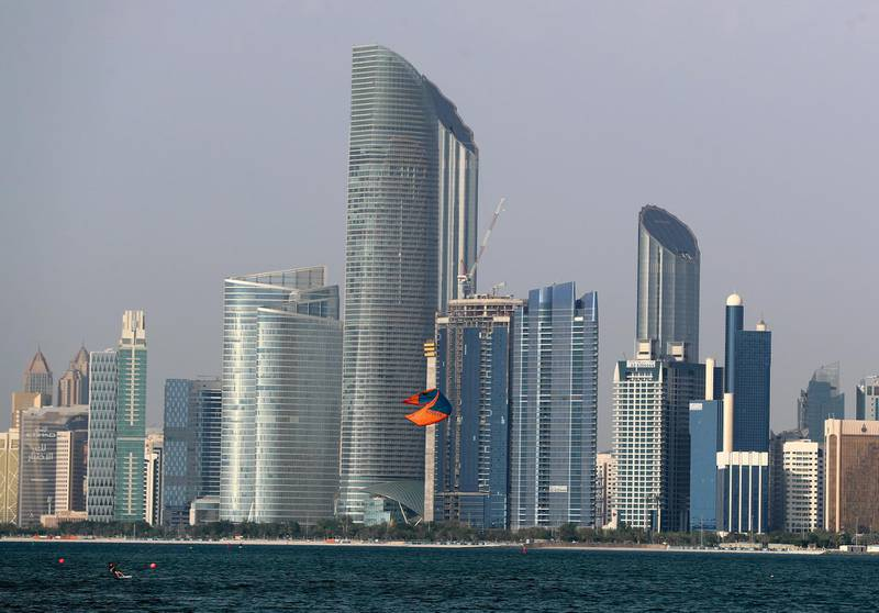 Abu Dhabi, United Arab Emirates - Reporter: N/A: Standalone. A kite surfer performs in the bay in front of the Abu Dhabi skyline at sunset. Monday, April 27th, 2020. Abu Dhabi. Chris Whiteoak / The National