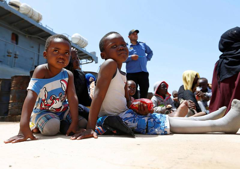 Migrants sit at a naval base after being rescued by Libyan coast guards in Tripoli, Libya June 29, 2018. REUTERS/Ismail Zitouny