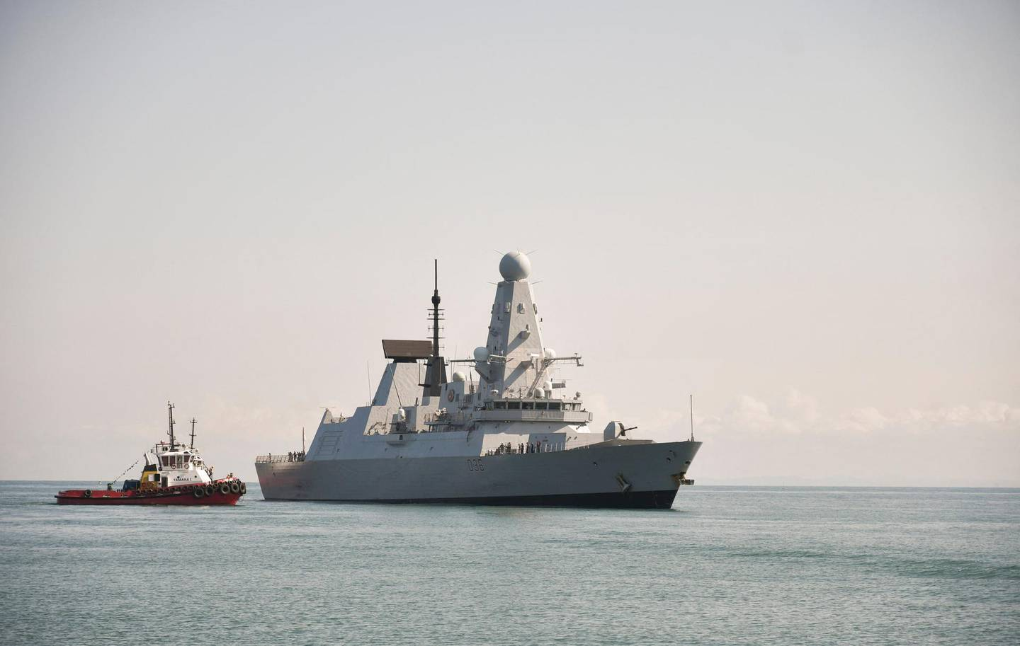 """This handout photo taken on June 26, 2021 and released by British Embassy in Georgia, shows the British Royal Navy destroyer HMS Defender arrives in the Black Sea port of Batumi on June 26, 2021.  British navy destroyer, HMS Defender, makes a port call in Georgia's Black Sea port of Batumi for joint exercises with the NATO-aspirant country's coast guard, according to the Royal Navy, days after Russia claimed it had fired warning shots at the warship in the coastal waters of Crimea. - RESTRICTED TO EDITORIAL USE - MANDATORY CREDIT """"AFP PHOTO /British Embassy in Georgia """" - NO MARKETING - NO ADVERTISING CAMPAIGNS - DISTRIBUTED AS A SERVICE TO CLIENTS  / AFP / Irakli GEDENIDZE / RESTRICTED TO EDITORIAL USE - MANDATORY CREDIT """"AFP PHOTO /British Embassy in Georgia """" - NO MARKETING - NO ADVERTISING CAMPAIGNS - DISTRIBUTED AS A SERVICE TO CLIENTS"""