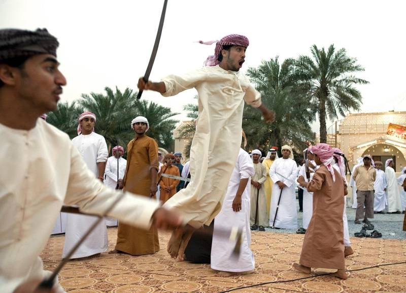 al Rams- April 17, 2009 - A young boy leaps into the air with his sword or Saif (CHECK SPELLING) during a mock battle with another boy during a traditional Arabic dance called the Razif at an Emirati wedding celebration for two grooms of the Shehhi tribe in the village of al Mahboobi in al Rams near Ras al Khaimah April 17, 2009.  The blades have been dulled to help prevent serious injury if one makes contact with the blade. (Photo by Jeff Topping/The National) *** Local Caption ***  JT002-0417-EMIRATI WEDDING IMG_6836.JPG
