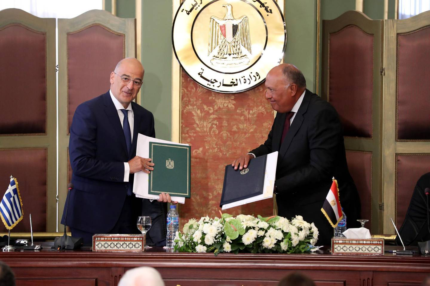 epa08587694 Greek Foreign Minister Nikos Dendias (L) and Egyptian Foreign Minister Sameh Shoukry (R) hold up signed documents after signing maritime border agreement in Cairo, Egypt, 06 August 2020. Egypt and Greece on 06 August signed an agreement to demarcate the maritime borders between the two countries.  EPA/KHALED ELFIQI