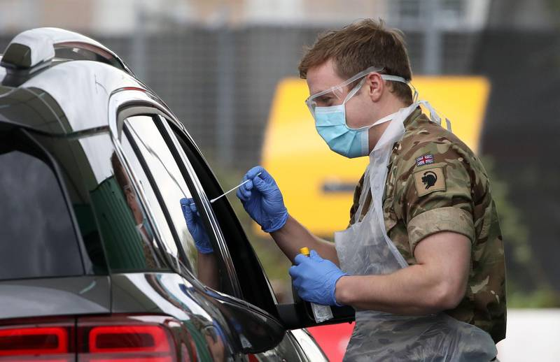 A soldier from 2 Scots Royal Regiment of Scotland  tests a key worker for the novel coronavirus Covid-19 at a drive-in testing centre at Glasgow Airport on April 29, 2020, as the UK continues in lockdown to help curb the spread of the coronavirus.  / AFP / POOL / Andrew Milligan