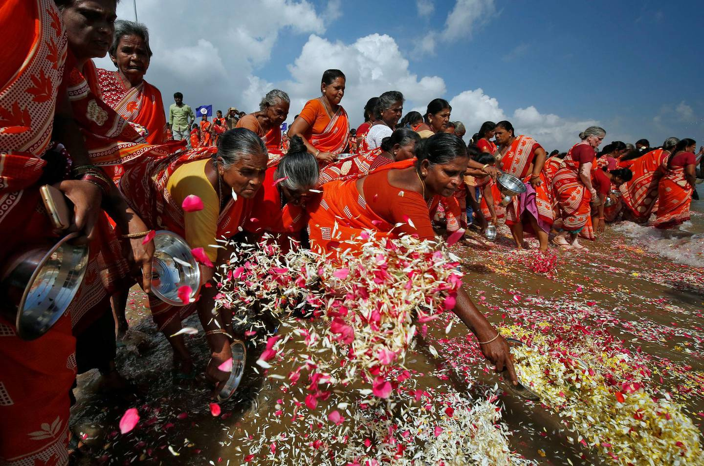 Women scatter flower petals in the waters of the Bay of Bengal during a prayer ceremony for the victims of the 2004 tsunami on the 15th anniversary of the disaster, at Marina beach in Chennai, India, December 26, 2019. REUTERS/P. Ravikumar