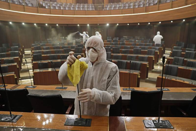 TOPSHOT - Sanitary workers disinfect the desks and chairs of the Lebanese Parliament in central Beirut on March 10, 2020 amid the spread of coronavirus in the country.  / AFP / ANWAR AMRO