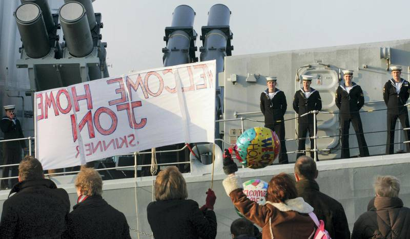 Family members wave to loved ones aboard the Royal Navy frigate HMS Richmond as she returns home to Portsmouth for Christmas today after an eventful seven-month security mission in the Arabian Gulf.   (Photo by Chris Ison - PA Images/PA Images via Getty Images)