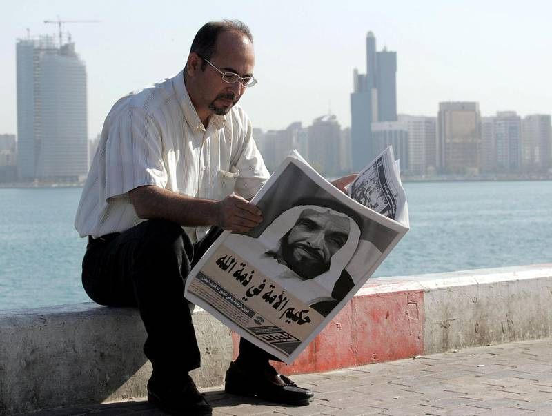 A man reads the newspapers with Sheikh Zayed bin Sultan al-Nahayan's portrait covering the whole front page during the funeral procession of the United Arab Emirate's late president in Abdu Dhabi 03 November 2004. Nahayan, the founding father of the Gulf emirates federation, died 02 November 2004 after more than 30 years at the helm of his oil-rich country.     AFP PHOTO/RABIH MOGHRABI / AFP PHOTO / RABIH MOGHRABI