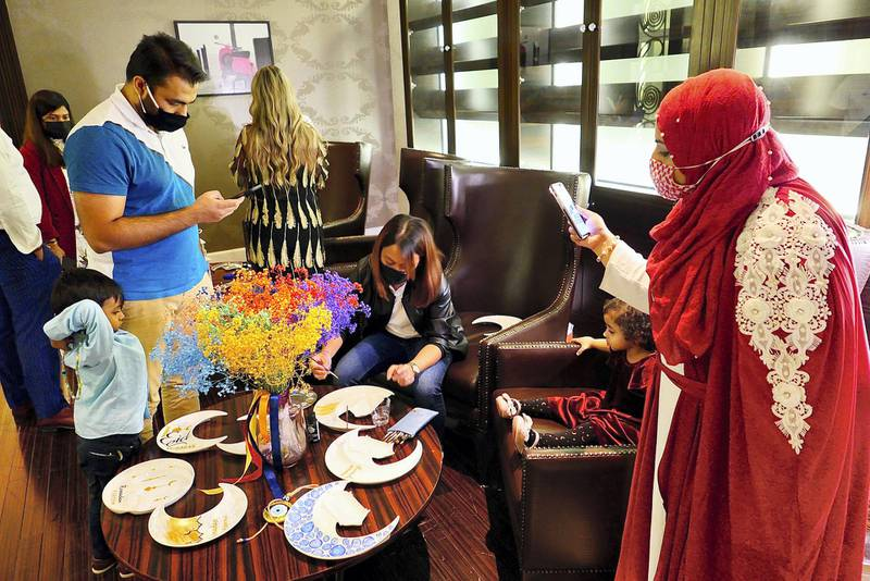 DUBAI, UNITED ARAB EMIRATES , April 15  – 2021 :- Guests making Ramadan-inspired sketch on the ceramic plates during the live demo given by Nancy Safy, a Dubai-based artist and founder of To Infinity & Beyond, a local small business well-known for their bespoke hand painted art during the Iftar held at Marriott Al Jaddaf in Dubai. ( Pawan Singh / The National ) For News/Online/Instagram/Standalone/Life Style