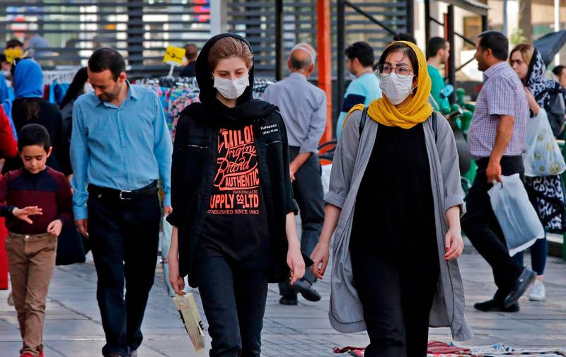 Iranians, some wearing face masks, walk along a street in the capital Tehran on June 3, 2020, amid the novel coronavirus pandemic crisis.  The spread of novel coronavirus has accelerated again this month in Iran which today officially confirmed over 3,000 new cases for a third consecutive day. / AFP / afp / -