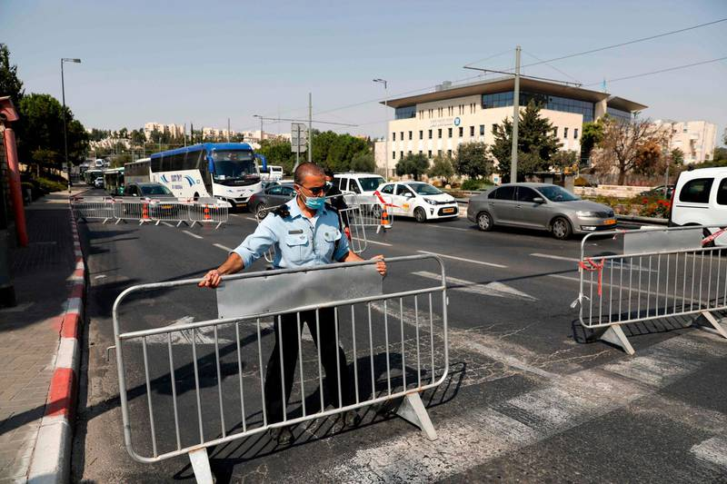 Members of the Israeli police set up barriers to traffic at a checkpoint in Jerusalem on September 18, 2020, to enforce a second lockdown amid the COVID-19 pandemic. Israel imposed a second nationwide lockdown to tackle one of the world's highest coronavirus infection rates, despite public protests over the new blow to the economy. The three-week shutdown from 2:00 pm (1100 GMT) started just hours before Rosh Hashana, the Jewish new year, and will extend through other key religious holidays, including Yom Kippur and Sukkot. / AFP / Ahmad GHARABLI