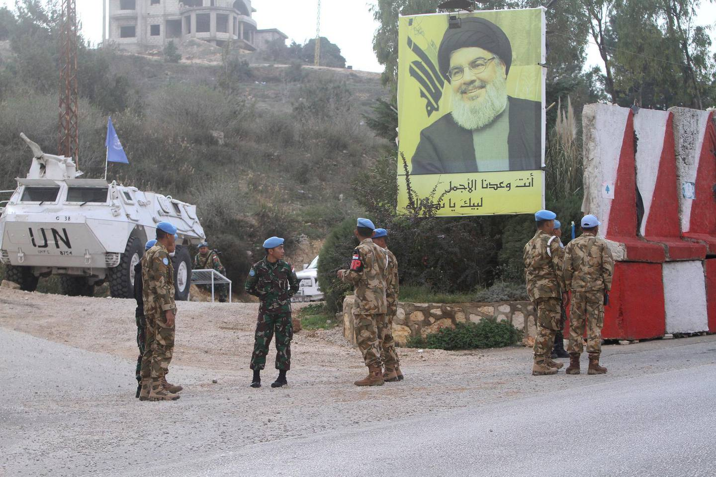 """Indonesian U.N peacekeepers stand in front a poster of Hezbollah leader Sheik Hassan Nasrallah, as they patrol the Lebanese side of the Lebanese-Israeli border in the southern village of Kfar Kila, Lebanon, Tuesday, Dec. 4, 2018. The Israeli military launched an operation on Tuesday to """"expose and thwart"""" tunnels it says were built by the Hezbollah militant group that stretch from Lebanon into northern Israel. (AP Photo/Mohammed Zaatari)"""