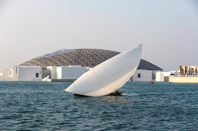 Abu Dhabi, United Arab Emirates, November 11, 2017:    A traditional dhow sails during the past the Louvre Abu Dhabi during the opening day on Saadiyat Island in Abu Dhabi on November 11, 2017. Christopher Pike / The National  Reporter: James Langton, John Dennehy Section: News