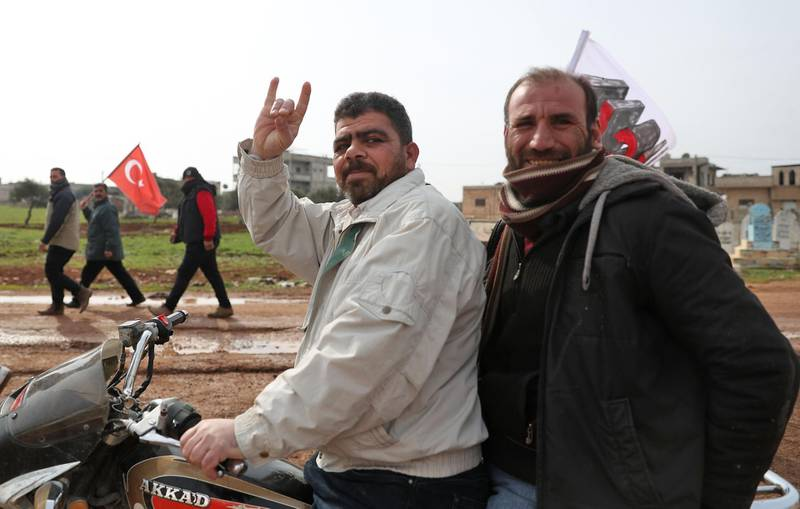 (FILES) In this file photo taken on February 14, 2020, a motorcycle rider flashes the Grey Wolves (a Turkish far-right ultranationalist organisation) gesture, as people behind him march with Turkish flags during a demonstration by a Turkish military observation post in the town of Binnish in Syria's northwestern province of Idlib, near the Syria-Turkey border. France is to ban a Turkish ultra-nationalist group known as the Grey Wolves, the interior minister said on November 2, after a memorial to the mass killings of Armenians was defaced at the weekend. The dissolution of the Grey Wolves will be put to the French cabinet on Wednesday, Gerald Darmanin told a parliamentary committee. / AFP / Omar HAJ KADOUR