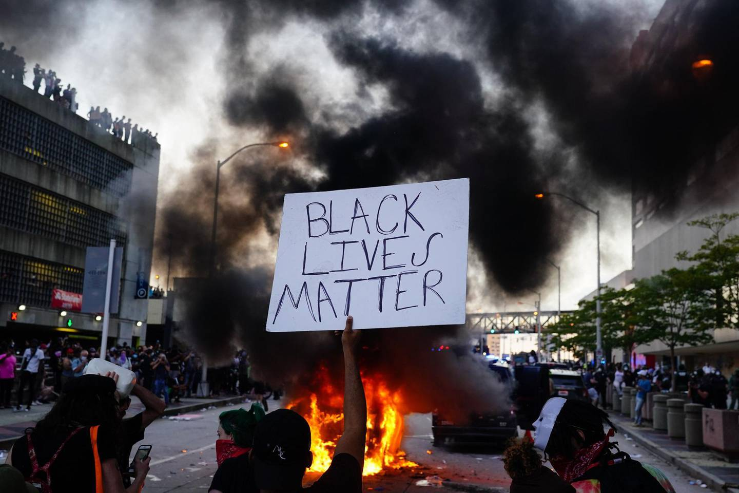 """(FILES) In this file photo a man holds a Black Lives Matter sign as a police car burns during a protest on May 29, 2020 in Atlanta, Georgia. When Ridley Scott and Kevin Macdonald created documentary """"Life in a Day"""" a decade ago, their goal was to construct a video portrait of a typical 24 hours on Earth, as filmed by tens of thousands of amateurs around the world. Repeating the trick in """"Life in a Day 2020,"""" stitching together footage shot last summer as the coronavirus pandemic and massive anti-racism protests turned the world on its head, their sequel is anything but typical. Assembled by a vast team of editors from 324,000 clips, the film -- which premieres February 1, 2021, at Sundance before hitting YouTube -- captures the eerily empty streets, collective cabin-fever and civil unrest of a year like no other. / AFP / GETTY IMAGES NORTH AMERICA / Elijah Nouvelage"""