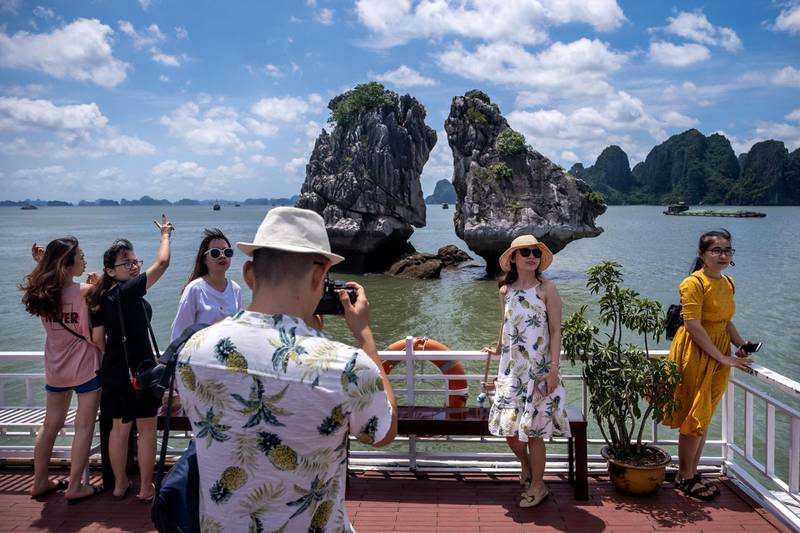 QUANG NINH, VIETNAM - MAY 31: Vietnamese tourists pose for photographs on a boat touring Ha Long Bay, after the Vietnamese government eased the lockdown following the coronavirus disease (COVID-19) outbreak, on May 31, 2020 in Ha Long, Quang Ninh Province, Vietnam. Though some restrictions remain in place, Vietnam has lifted the ban on domestic travel, certain entertainment facilities and non-essential businesses to revive its economy. As of May 31, Vietnam has confirmed 328 cases of coronavirus disease (COVID-19 ) with no deaths in the country, 279 fully recovered and no new case caused by community transmission for 46 days. (Photo by Linh Pham/Getty Images)
