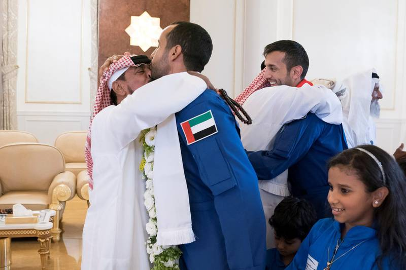 ABU DHABI, UNITED ARAB EMIRATES - October 12, 2019: The Father of Hazza Ali Al Mansoori, the first UAE Astronaut to be deployed on a space mission to the International Space Station (ISS) (R) greets his son during a homecoming reception at the Presidential Airport. Seen with Sultan Saif Al Neyadi, a member of the International Space Station (ISS) mission back-up team (L).   ( Mohamed Al Hammadi / Ministry of Presidential Affairs ) ---