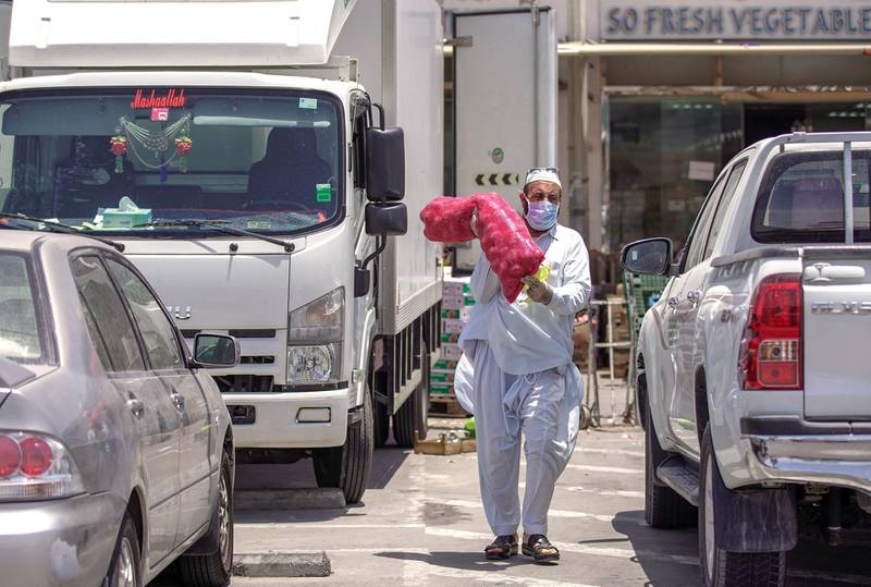 Abu Dhabi, United Arab Emirates, May 7, 2020.  A man carries a sack of onions at the open section of the Al Mina Vegetables and Fruits Market during the time of Ramadan and the Coronavirus pandemic.Victor Besa/The NationalSection:  NAReporter:
