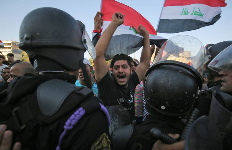 Iraqi protesters shout slogans and wave national flags as they facing security forces  during clashes at a demonstration against unemployment and a lack of basic services in the capital Baghdad's Tahrir Square on July 20, 2018.  / AFP / AHMAD AL-RUBAYE