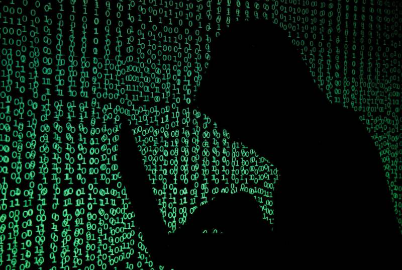FILE PHOTO: A hooded man holds a laptop computer as cyber code is projected on him in this illustration picture taken on May 13, 2017. REUTERS/Kacper Pempel/Illustration/File Photo