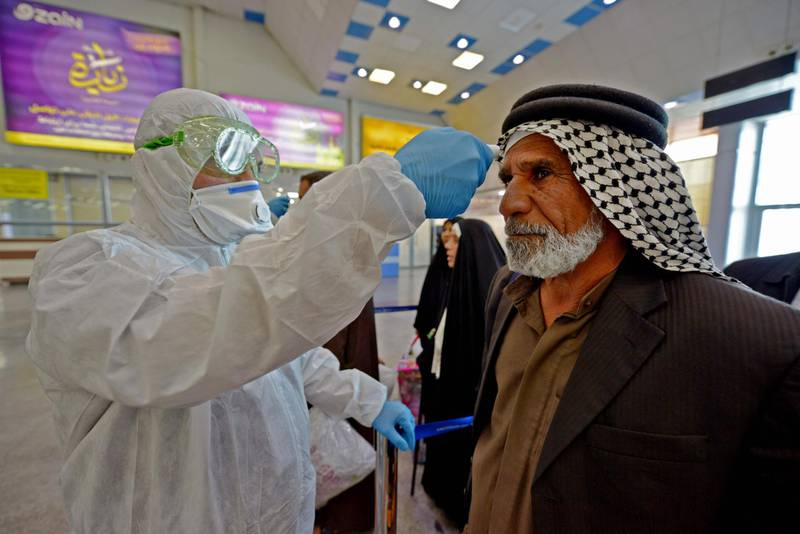 The body temperature of an Iraqi man returning from Iran is measured upon her arrival at the Najaf International Airport on February 21, 2020, after Iran announced cases of coronavirus infections in the Islamic republic.  / AFP / Haidar HAMDANI