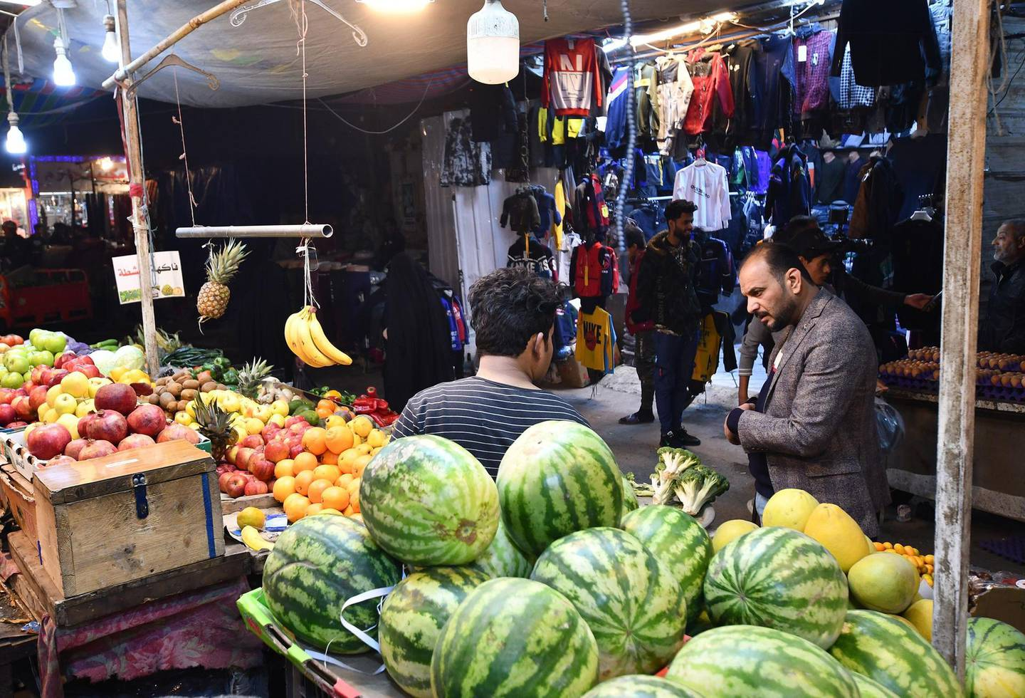 A man talks to a fruit vendor at a market in the southern Iraqi city of Nasiriyah in the Dhi Qar province, on December 20, 2020.  A year of economic agony for pandemic-hit and oil-reliant Iraq is drawing to a close, but a draft 2021 budget involving a hefty currency devaluation could bring more pain for citizens. Iraq, which relies on oil sales to finance 90 percent of its budget, projects that its economy has shrunk by 11 percent this year, while poverty doubles to 40 percent of the country's 40 million residents. / AFP / Asaad NIAZI