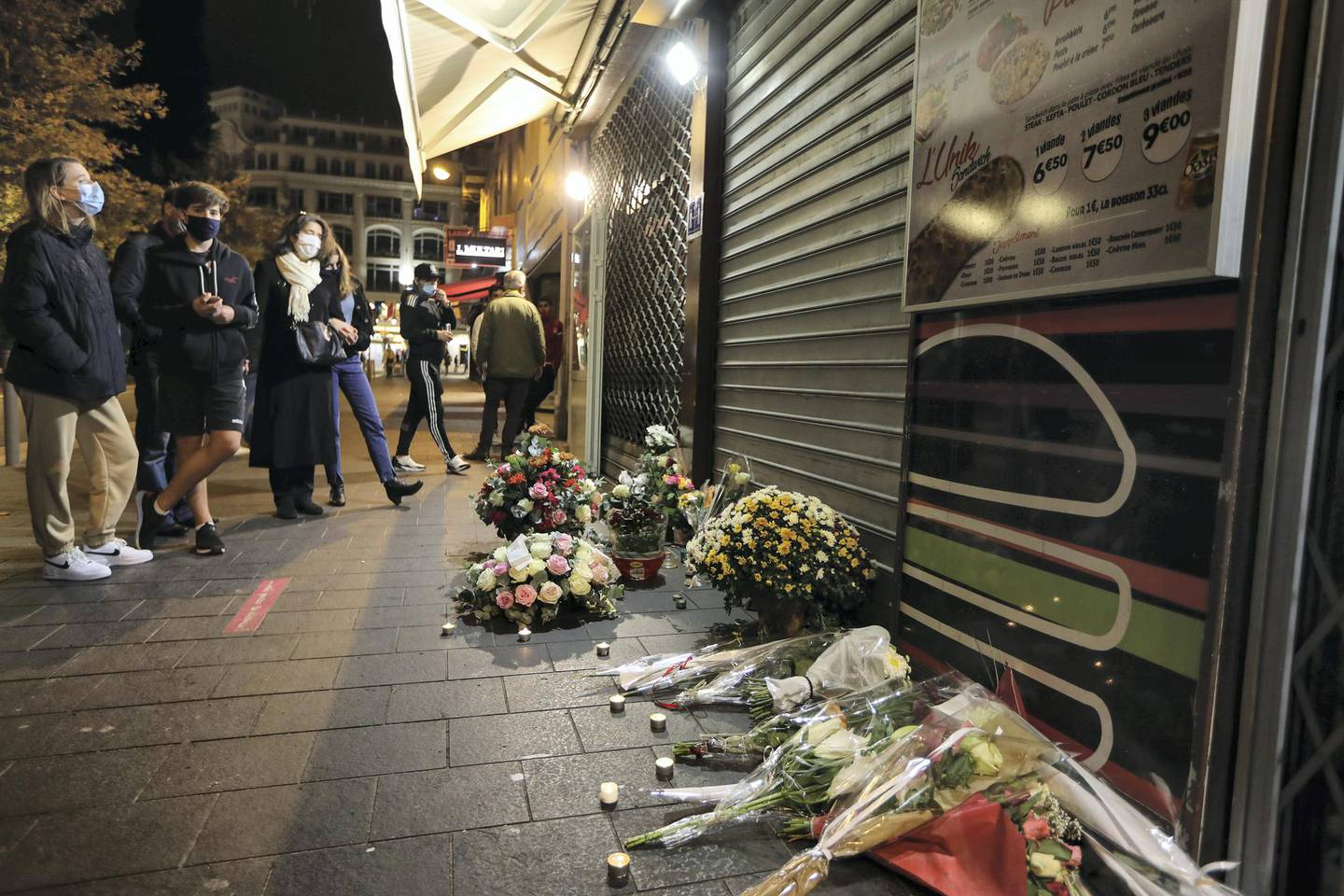 Flowers have been laid outside the restaurant where Brazilian Simone Barreto Silva took refuge after being stabbed several times but died of her wounds there, near Notre-Dame de l'Assomption Basilica in Nice on October 31, 2020, two days after a knife attacker killed three people (including Barreto Silva), cutting the throat of two, inside the church of the French Riviera city, and police arrest a young Tunisian migrant from Sfax who arrived in Europe only last month, according to French prosecutors. - The killings came two weeks after a French teacher was decapitated outside his school north of Paris by a suspected Islamist extremist. The teacher had shown his pupils cartoons of the Prophet Mohammed during a lesson on freedom of speech. (Photo by Valery HACHE / AFP)