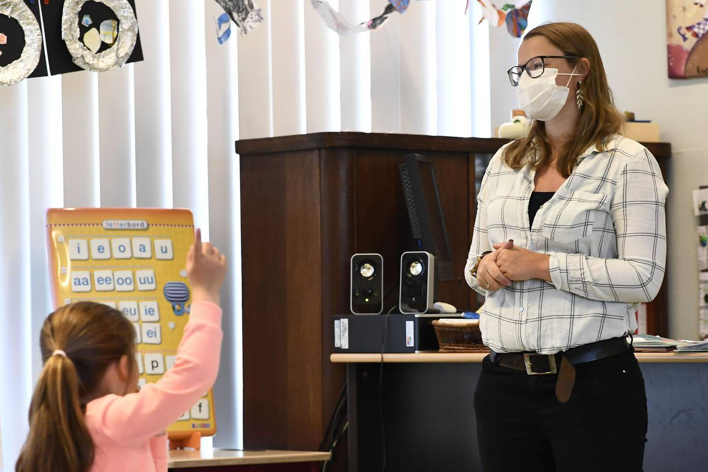 A teacher wearing a mask gives class at Olfa Elsdonk primary school in Edegem, Antwerp, on May 15, 2020 as schools test the re-opening and start again for a limited number of grades on May 18 amid the pandemic of novel coronavirus (COVID-19).  Belgium is in its ninth week of confinement.   - Belgium OUT  / AFP / Belga / DIRK WAEM