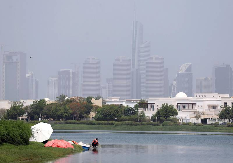 Dubai, United Arab Emirates - July 18, 2019: Weather. Men work to fix a fountain on a hot humid day in Dubai. Thursday the 18th of July 2019. The Springs, Dubai. Chris Whiteoak / The National