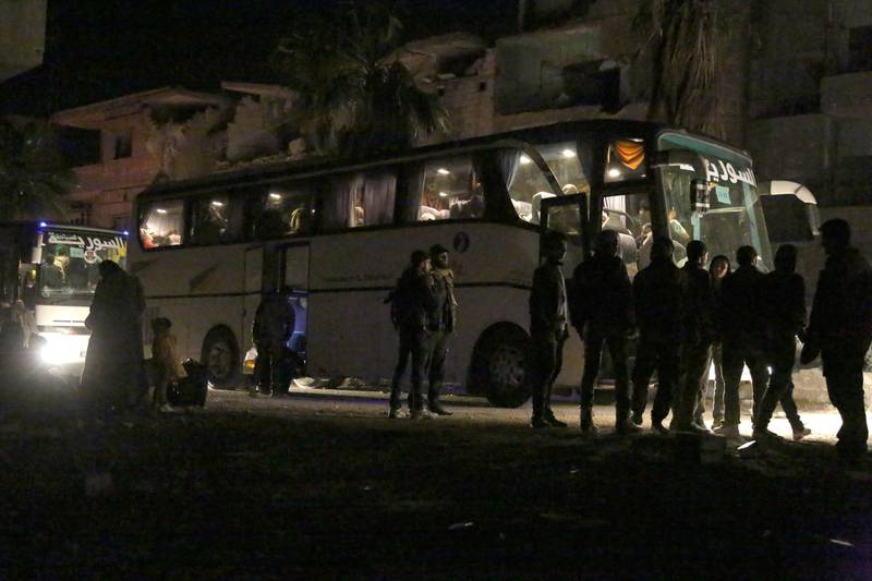 Syrians gather as they prepare to board a bus to evacuate one of the few remaining rebel-held pockets in Arbin, in Eastern Ghouta, on the outskirts of the Syrian capital Damascus, on March 24, 2018. Syrian rebels and civilians prepared to evacuate the penultimate opposition-held pocket of Eastern Ghouta, as the government moved ever closer to securing the outskirts of the capital. / AFP PHOTO / Ammar SULEIMAN