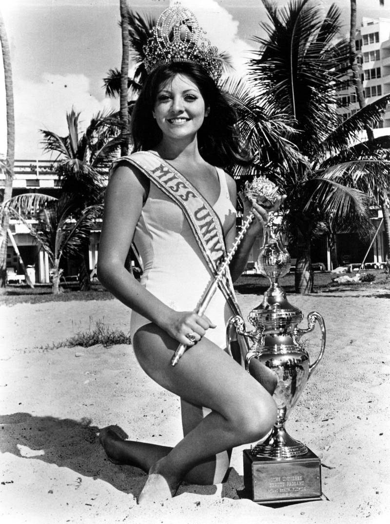 Posing with some of her prizes, Georgia Risk, Miss Universe 1971, smiles for the photographer.  Although Miss Universe no longer receives a trophy or sceptor, she does receive a specially designed Hoya Crystal statue. Courtesy Miss Universe