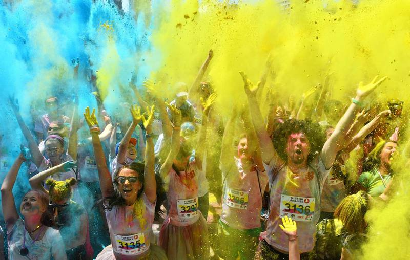 People take part in the Kyiv Color Run in Kiev on June 10, 2018.   From the first event in the United States in January 2012 The Color Run has since spread across the globe leaving a trail of color and happy runners. / AFP / Sergei SUPINSKY