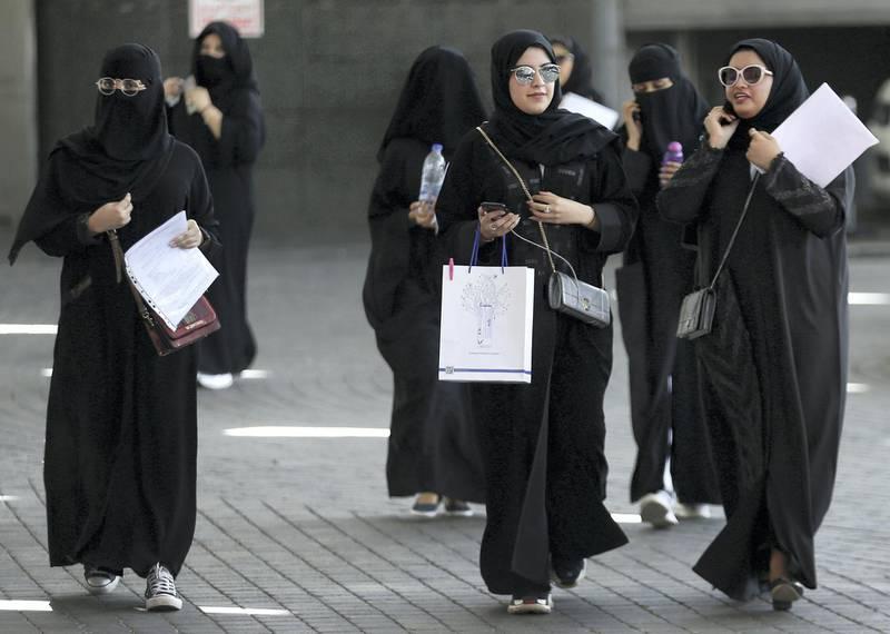 Saudi students walk at the exhibition to guide job seekers at Glowork Women's Career Fair in Riyadh, Saudi Arabia October 2, 2018. REUTERS/Faisal Al Nasser
