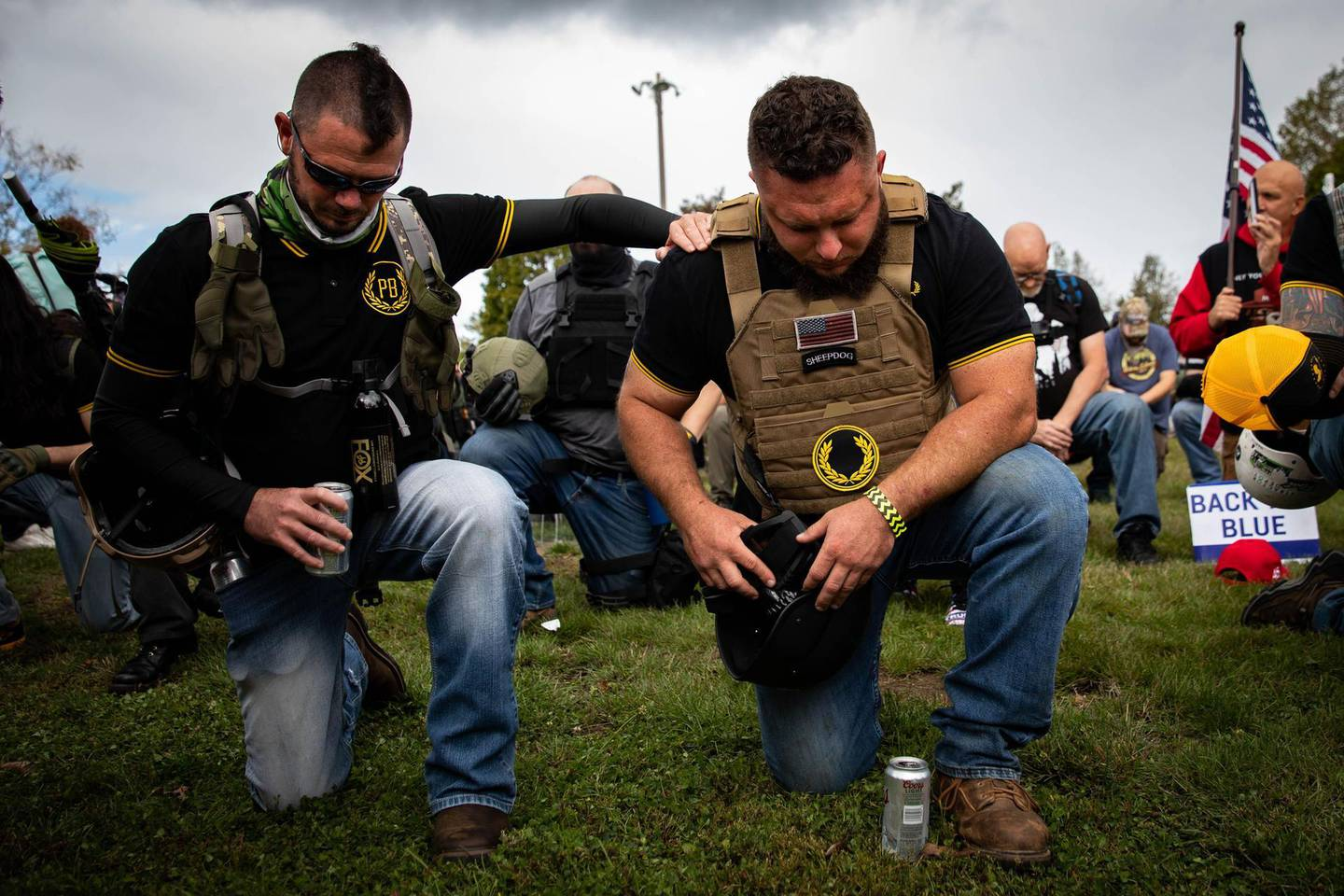 """People take a knee as an organizer reads a prayer to the crowd of several hundred gathered during a Proud Boys rally at Delta Park in Portland, Oregon on September 26, 2020. Far-right group """"Proud Boys"""" members gather in Portland to show support to US president Donald Trump and to condemn violence that have been occurring for more than three months during """"Black Lives Matter"""" and """"Antifa"""" protests.   / AFP / Maranie R. STAAB"""