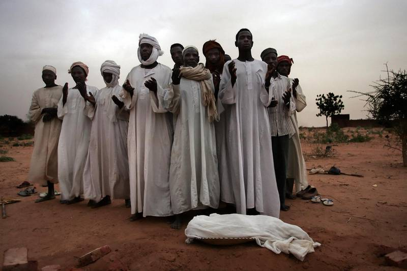 Relatives mourn over the body of 1-year-old Ali, who died of malnutrition 21 June 2004 in a refugee camp in El-Geneina in the Darfour, Sudan. More than 80,000 displaced people reached Mornay to try to escape ethnic violence in the Darfur region. After surviving massacres carried out by pro-government militias on their villages, these refugees are now virtual prisoners in the camp as the same militias now control the camp's periphery conducting violent attacks and rapes on villagers who go out looking for food and essential items according to Medecins Sans Frontiers (MSF) (Doctors without Borders) the French medical charity.  AFP PHOTO/MARCO LONGARI (Photo by Marco LONGARI / AFP)