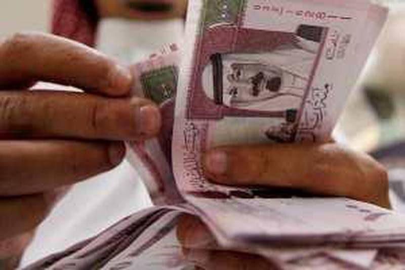 A Saudi banker counts new one hundred riyals bearing the portrait of Saudi King Abdullah bin Abdul Aziz al-Saud at a bank in Riyadh, 05 June 2007. The banknotes featuring the king are the fifth issue released by the Saudi Arabian Monetary Agency (SAMA). AFP PHOTO/HASSAN AMMAR