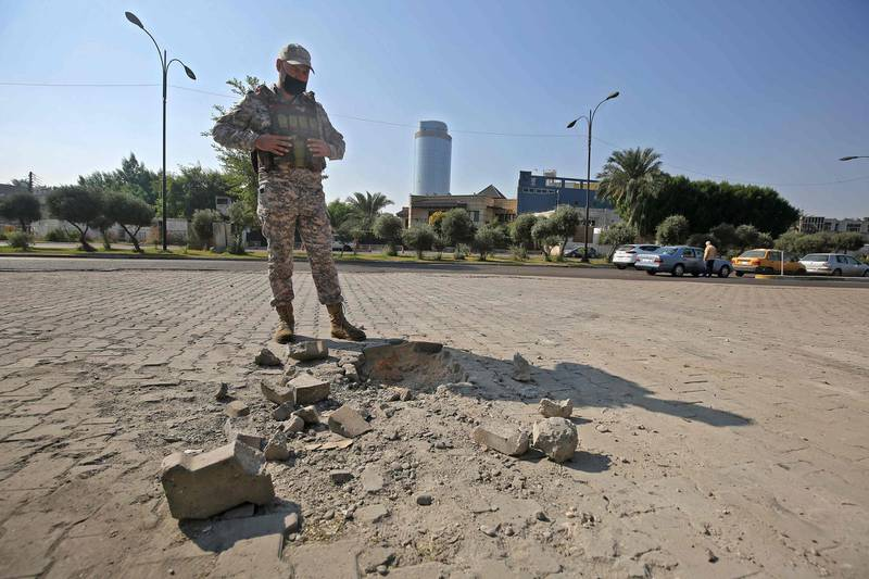 A member of the Iraqi security forces inspects the damage outside the Zawraa park in the capital Baghdad on November 18, 2020, after volley of rockets slammed into the Iraqi capital breaking a month-long truce on attacks against the US embassy.  According to the Iraqi military, four of the rockets landed in the high-security Green Zone, where the US embassy and other foreign missions are based.  Another three rockets also hit other parts of Baghdad, killing one girl and wounding five civilians. All seven rockets were launched from the same location in east Baghdad, the Iraqi military said in a statement. / AFP / AHMAD AL-RUBAYE
